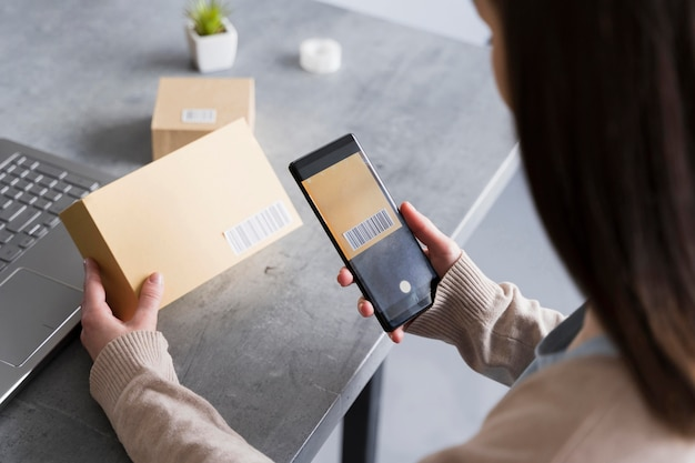Высокий угол женщина сканирования штрих-кода на коробке с смартфон