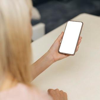 Высокий угол обзора женщины, использующей смартфон дома во время пандемии