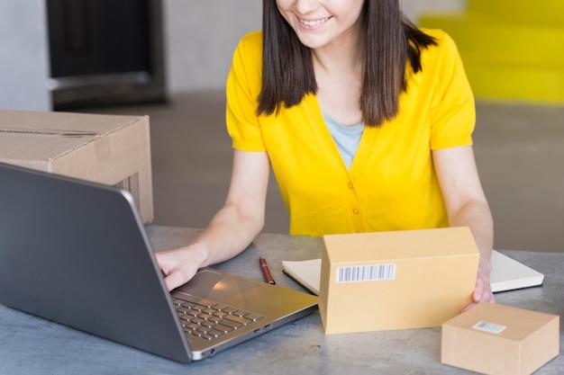 Высокий угол женщины с коробками и ноутбуком