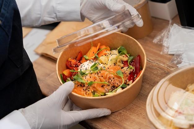 持ち帰り用のサラダを梱包する手袋を持つ女性の高角度 Premium写真