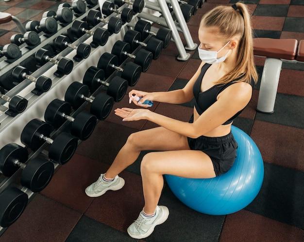 Женщина с медицинской маской тренируется в тренажерном зале и использует дезинфицирующее средство для рук