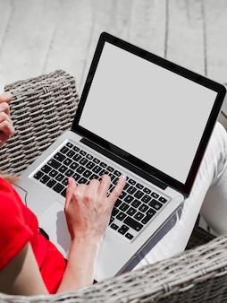 Высокий угол женщины, работающие на ноутбуке на открытом воздухе