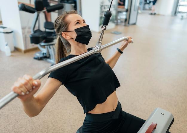 유행병 동안 체육관에서 운동하는 여성의 높은 각도