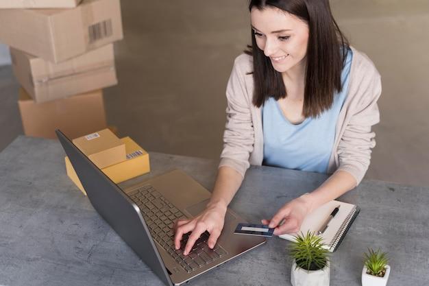 Высокий угол женщины, работающие с ноутбуком и коробки