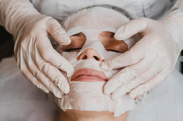 Высокий угол молодой красивой женщины, получающей лечение маски для кожи