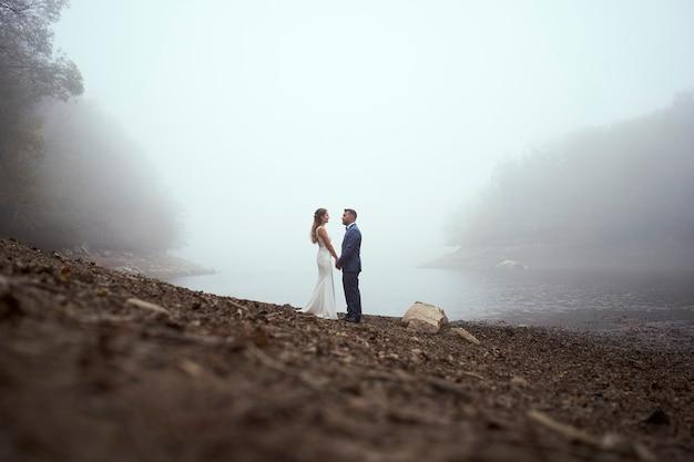 手をつないでお互いを見ているウェディングドレスの若いカップルの高角度