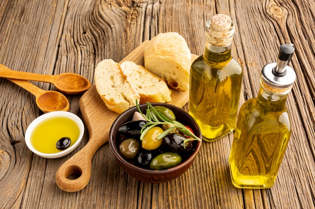 High angle olives mix bread and oil bottles