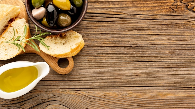 High angle olives mix bread and oil saucer with copy space