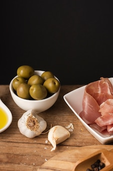 High angle olives and prosciutto on cutting board