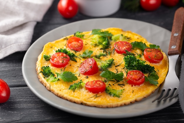 High angle of omelette for breakfast with tomatoes and herbs