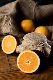 Alto angolo di arance con tela e barattolo di marmellata