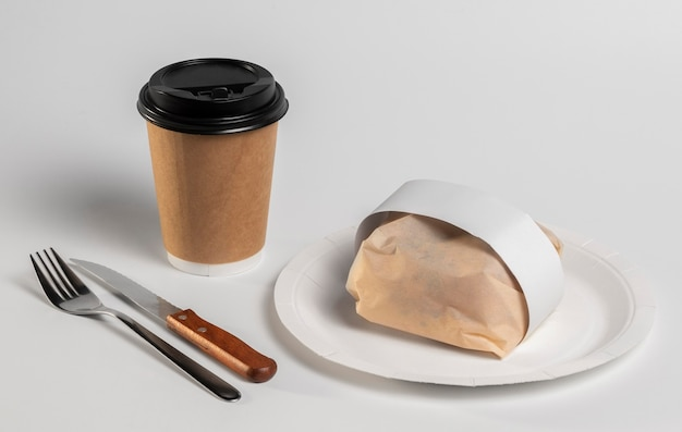 High angle packaged burger on plate with coffee cup and cutlery