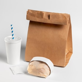 High angle packaged burger with cup and paper bag