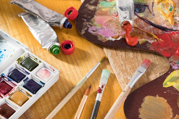 High angle of paint brushes with palette and paint