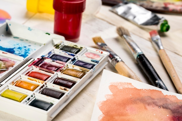High angle of paint palette and brushes