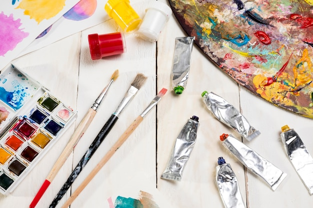 High angle of paint palette and tubes with brushes