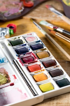 High angle of paint palette with brushes and colors
