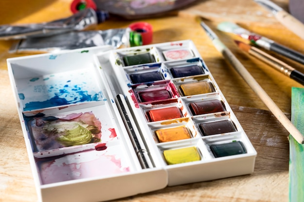 High angle of paint palette with brushes