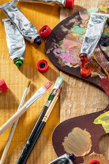 High angle of paint tubes with brushes and palette