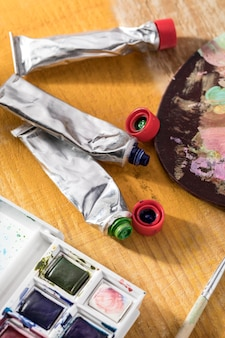 High angle of paint tubes with palette