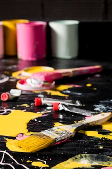 High angle of painting brushes with paint cans