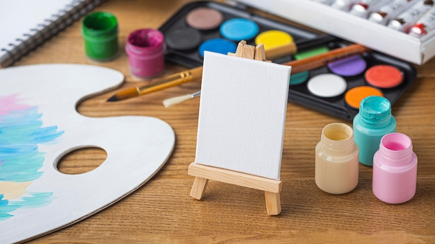High angle of painting essentials with easel and palette