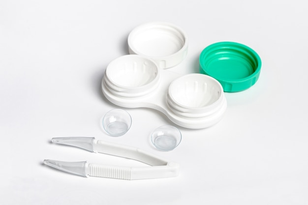 High angle of pair of contact lenses with case and tweezers