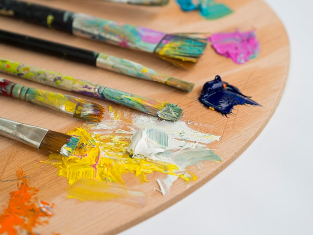 High angle of palette with paint brushes