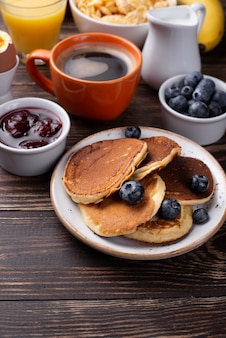 High angle of pancakes for breakfast on plate with blueberries and coffee