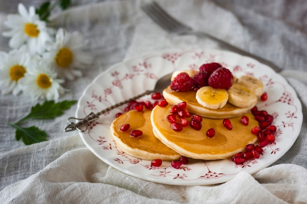 High angle pancakes with pomegranate seeds bananas and raspberries