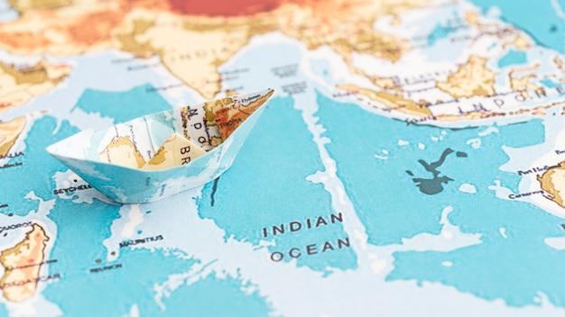 世界地図上の高角度の紙の船