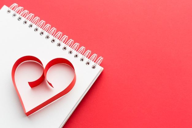 High angle of paper heart shape on notebook with copy space