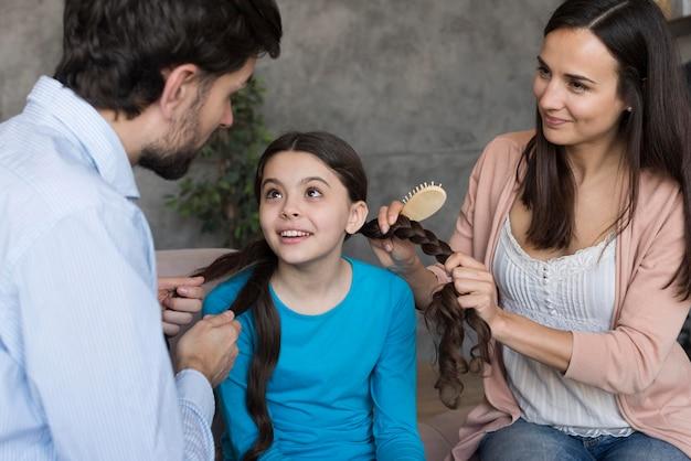ハイアングルの両親が娘の髪をブラッシング