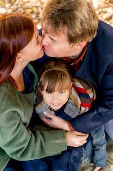 Родители под высоким углом целуются на открытом воздухе