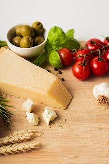 まな板の上の高角度のパルメザンチーズトマトとニンニク