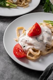 Alto angolo di piatto di pasta con condimento e pomodori