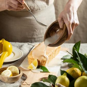 Angolo alto del pasticcere che aggiunge condimento alla torta al limone