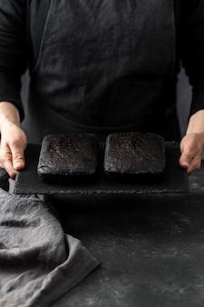 Angolo alto del pasticcere che tiene due pezzi di torta