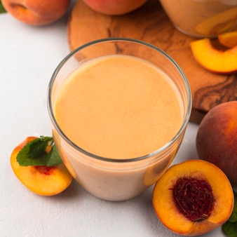 High angle of peach milkshake glass with fruit