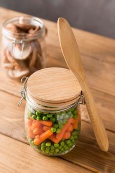 Alto angolo di piselli e carotine in vaso di vetro con cucchiaio