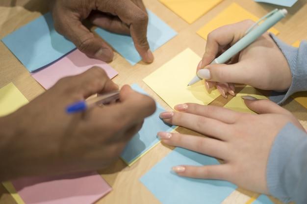 Elevato angolo di persone in ufficio scrivendo idee su foglietti adesivi
