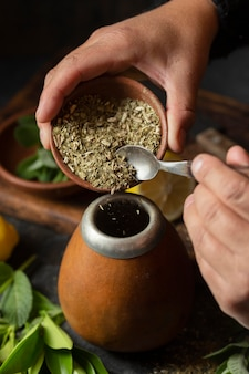 High angle person adding herbs into infuser