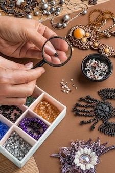 High angle of person doing bead work with magnifying glass