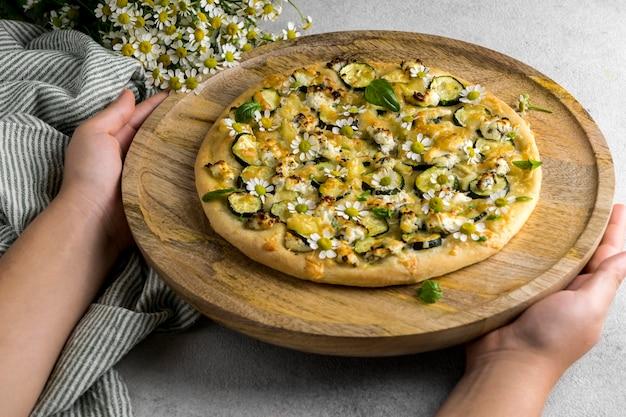 Alto angolo di persona che tiene una deliziosa pizza cotta con bouquet di fiori di camomilla