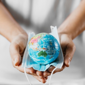High angle of person holding medical mask with earth globe