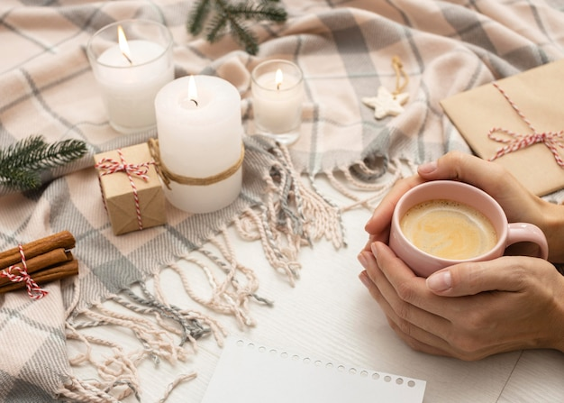 High angle of person holding mug with blanket and candles