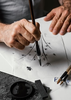 High angle person painting with chinese ink on white paper