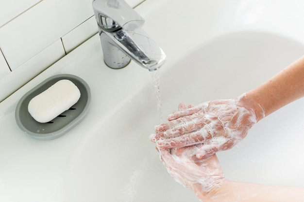 High angle of person washing hands at the sink