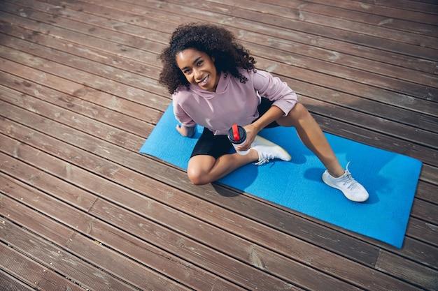 Фото под высоким углом афроамериканской женщины, сидящей на коврике для йоги и смотрящей в камеру