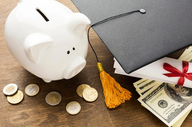 High angle of piggy bank with academic cap and coins